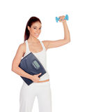 Happy girl in white toning her muscles and with a scale Royalty Free Stock Photo