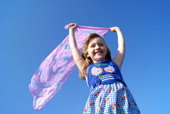 The happy girl on a wind. The laughing girl in a dress against the dark blue sky holds over a head an easy female scarf fluttering on a wind and looks forward Royalty Free Stock Images