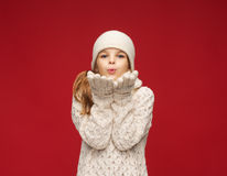 Happy girl in winter clothes blowing on palms Stock Photo