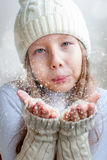 Happy girl in winter clothes blowing on palms Winter happiness a Stock Photos