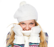 Happy girl in winter clothes hiding in scarf. Isolated on white Royalty Free Stock Photo