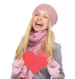 Happy girl in winter hat and scarf with heart shaped postcard Stock Image