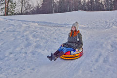 Happy girl on a winter sleigh ride. Happy teenage girl enjoying a winter sleigh ride on a slope Stock Images