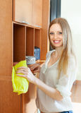 Happy girl wipes the dust from furniture Royalty Free Stock Photo