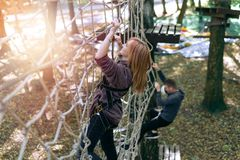Happy girl, woman, climbing gear in an adventure, rope road, insurance, attraction, amusement park, active recreation, autumn royalty free stock image