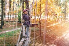 Happy girl, woman, climbing gear in an adventure, rope road, insurance, attraction, amusement park, active recreation, autumn stock image
