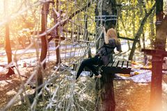 Happy girl, woman, climbing gear in an adventure, rope road, insurance, attraction, amusement park, active recreation, autumn stock photography