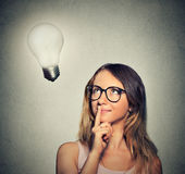 Happy girl woman thinks looking up at bright light bulb Royalty Free Stock Photography