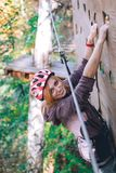 Happy girl, women, climbing gear in an adventure park are engaged in rock climbing on the rope road, arboretum, insurance,. Attraction, amusement park, active stock photos
