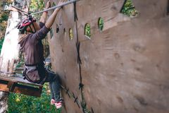 Happy girl, women, climbing gear in an adventure park are engaged in rock climbing or pass obstacles on the rope road, arboretum, royalty free stock photo