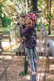 Happy girl, women, climbing gear in an adventure park are engaged in rock climbing on the rope road, arboretum, insurance,. Attraction, amusement park, active royalty free stock image