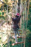 Happy girl, women, climbing gear in an adventure park are engaged in rock climbing on the rope road, arboretum, insurance, stock image