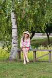 Happy girl on a wooden bench near the birch tree Royalty Free Stock Photography