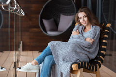 Happy girl wrapped in knitted coverlet sitting on the chair Royalty Free Stock Photos
