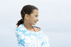 Happy Girl Wrapped In Towel Looking Away At Beach Stock Photo