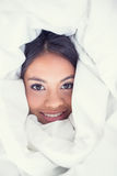 Happy girl wrapped up in her duvet smiling at camera Royalty Free Stock Photos