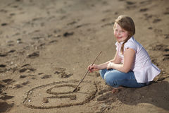 Happy girl writing number in the sand Stock Photo