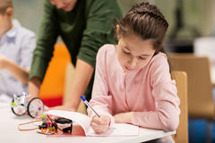 Happy girl writing to notebook at robotics school Royalty Free Stock Image