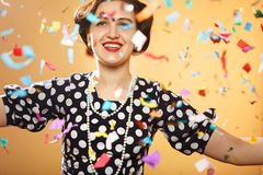 Girl with confetti. Happy girl on yellow background, colorful confetti slowly scatter and fall Stock Photos