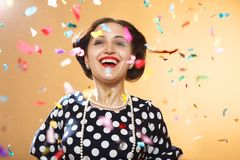 Girl under confetti. Happy girl on yellow background, colorful confetti slowly scatter and fall Royalty Free Stock Photos