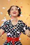 Girl under confetti. Happy girl on yellow background, colorful confetti slowly scatter and fall Stock Photo