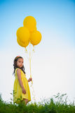 Happy girl with yellow balloons royalty free stock photography