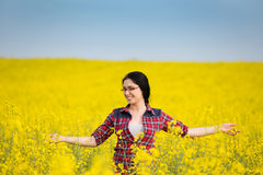 Happy girl in yellow blossom rapeseed field Stock Photo