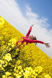 Happy girl in yellow field. Happy young woman in the yellow rape field Royalty Free Stock Images