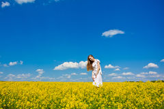 Happy girl in yellow flowers Stock Image