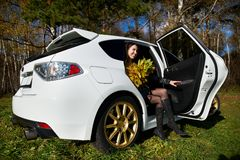 Happy girl with yellow leaves in white stylish car Stock Photo