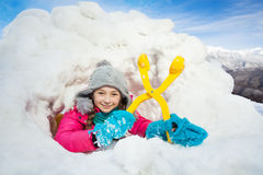 Happy girl with yellow snowmaker in the snow igloo Royalty Free Stock Image