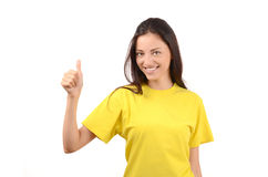Happy girl with yellow t-shirt signing thumbs up. Stock Photo