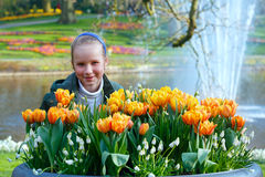 Happy girl with yellow tulips. Stock Images