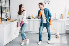 happy girlfriend and boyfriend in rubber gloves having fun with mop royalty free stock image
