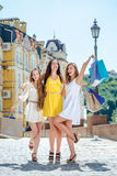 Happy girlfriend enjoyed discounts. Three friends holding shoppi Royalty Free Stock Images