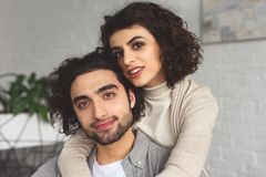 Happy girlfriend hugging boyfriend and they looking at camera. At home royalty free stock image