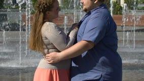Happy girlfriend hugging her overweight boyfriend, enjoying romantic date. Stock footage stock video