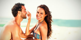 Happy girlfriend putting sunscreen on boyfriends nose Stock Photo