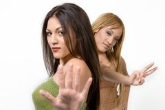 Happy girlfriends. Two young women pose together, with one holding out her palm and the other making a peace sign Stock Photos