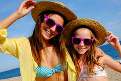 Happy girlfriends on beach with hats and sunglasses. Stock Photos