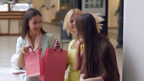 Happy girlfriends discuss new purchases in packages from expensive boutiques in season of sales and discounts. On Black Friday stock footage