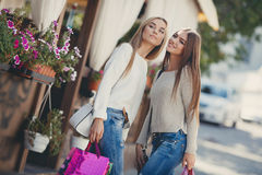 Happy girlfriends go shopping at the mall Stock Photography