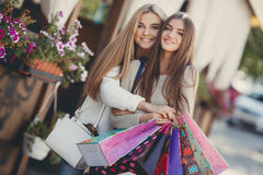 Happy girlfriends go shopping at the mall Royalty Free Stock Images