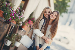 Happy girlfriends go shopping at the mall Stock Images