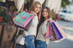 Happy girlfriends go shopping at the mall Royalty Free Stock Photos