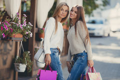 Happy girlfriends go shopping at the mall Stock Image