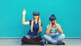 Happy girlfriends playing on vr glasses indoor stock photo