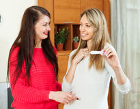 Happy girlfriends with pregnancy test Stock Photo