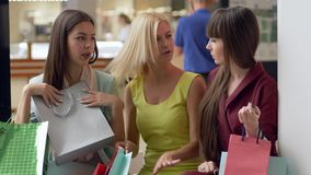 Happy girlfriends at shopping discuss new purchases in packages from expensive boutiques in season of sales and. Discounts on Black Friday stock video footage