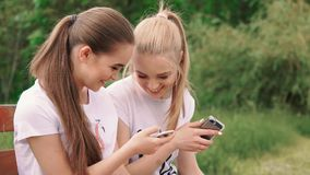 Happy girlfriends with smartphone. In the park stock footage